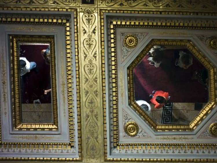 Visitors are reflected in the mirror-patched ceilings. Source: AP